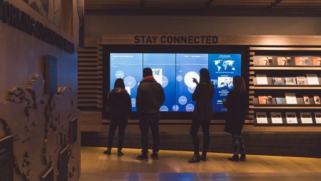 Os visitantes se reúnem em torno de uma parede de mídia social multiusuário